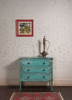 White brick wall and antique copper tea pot on vintage turquoise cabinet and hanged painting