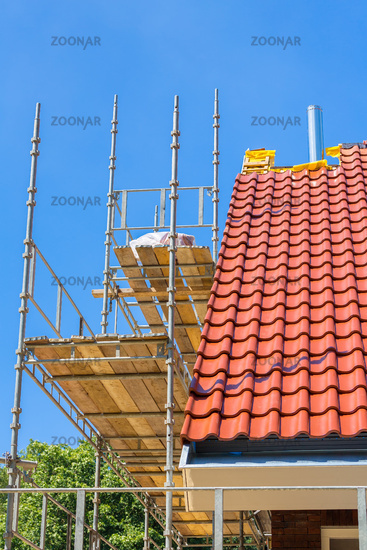 New house roof with scaffolding and blue sky
