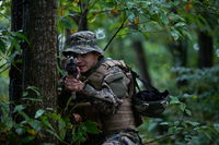 soldier in action aiming  on weapon  laser sight optics