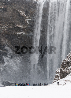 Skogafoss waterfall in Iceland on a snowing day with tourists around