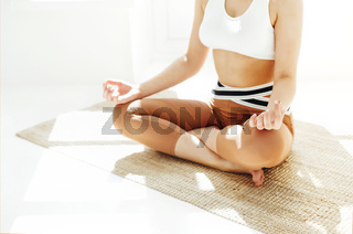 Нщгтп female in sportswear sitting with crossed legs and on mat and doing yoga