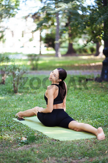 Athletic young woman doing yoga in the Park in the morning.