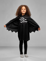 girl in costume of dracula with cape on halloween