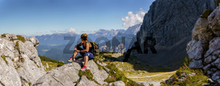 Woman sitting on a small hill in a beautiful mountain landscape