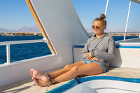 Young woman sits on boat at blue sea