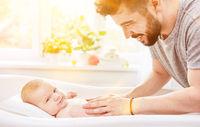 Vater badet Baby in Babybadewanne