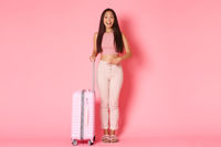 Travelling, holidays and vacation concept. Full-length of beautiful asian girl tourist in summer clothes pointing finger at suitcase and smiling pleased, recommend it over pink background