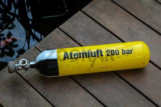Ein Taucherflasche mit Atemluft liegt auf dem Bootssteg.