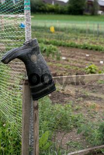 Arbeitsschuhe hängen am Gartenzaun - Gummistiefel