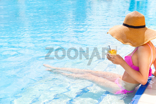Pretty woman in a hat enjoying cocktail in a swimming pool