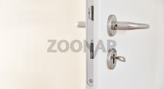 Zimmertür mit Klinke und Schlüssel im Türschloss