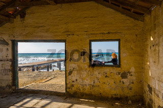 Pier and people through windows of abandoned buildiing in Argaka in Cyprus.