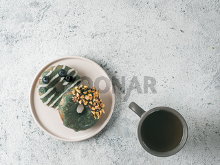 Vegan donuts topped spirulina glaze and tea