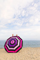 Happy at thbe beach behind Beach umbrella for shadow