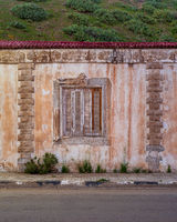 Aged house with weathered ornamental wall and shuttered window under green hill by asphalt road