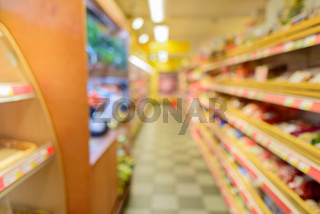Defocused supermarket aisle with shelves filled with grocery and checkered floor