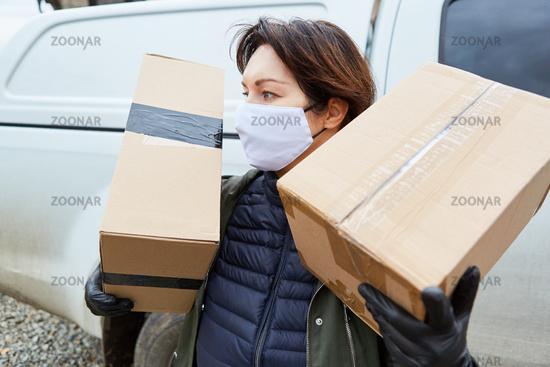 Paketbotin mit Mundschutz und Paketen zur Auslieferung