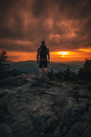 Hiker with backpack standing on mountain and enjoying sunset