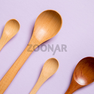 Wooden spoons on purple background