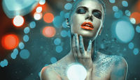 Beautiful woman with creative bright make-up over glowing lights background