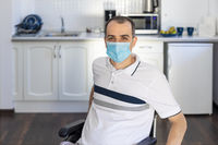 Smiling Young Handicapped Man Sitting On Wheelchair In Kitchen