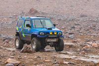 Japanese SUV Suzuki Jimny driving on rocky mountain road on background volcanic landscape. Active vacation, travel destinations, off-road trip in rainy weather
