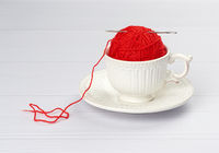 ball with a red woolen thread and a needle lies in a white ceramic cup