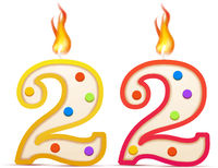 Twenty two years anniversary, 22 number shaped birthday candle with fire isolated on white