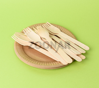 wooden fork and empty round brown disposable plate made from recycled materials on a green background