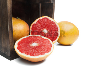 Fresh red grapefruits in a wooden box on a white