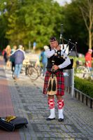Street musician with bagpipe on the beach promenade of Swinoujscie in Poland