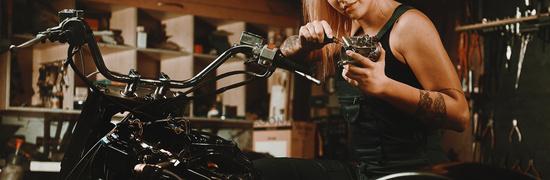 Woman mechanic repairing a motorcycle in workshop