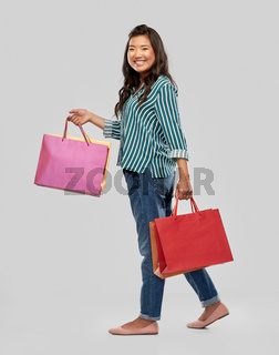 happy asian woman walking with shopping bags