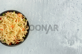 Instant noodles with carrot and scallions, vegetable soba bowl, top-down closeup shot