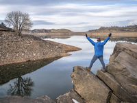 happy hiker on a hore of mountain lake at foothills of Rocky Mountains