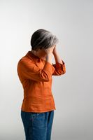 Dejected or depressed mature grey haired woman in orange shirt looks down holding her forehead with two hands. Pretty mid aged grey haired woman in orange shirt isolated on grey background