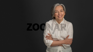 Senior woman laughing on grey background. Portrait of mature grey haired woman in white casuals looking happy on camera