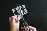 Family divorce. Cropped image of hand cutting paper family with scissors over wooden table.