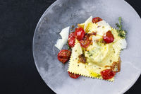 Traditional Italian ravioli pasta offered with parmesan cheese and fried tomatoes as top view on a modern design plate with copy space left