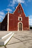 Catholic red colonial church Itzimna in a park, Merida, Yucatan, Mexico