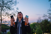 Young guy in the park takes a photo on two smartphones