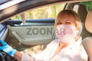 Seniorin mit Mundschutz am Steuer ihres Autos für Coronavirus Hausbesuch