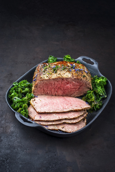 Traditional Commonwealth Sunday roast with sliced cold cuts roast beef with kalette and herbs as closeup on a modern design pan