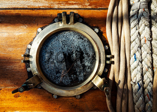 Vintage ship brass porthole and ropes