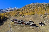 Der Weiler Le Louché am Fuss eines Lärchenwaldes in leuchtenden Herbstfarben