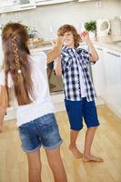 Kinder kämpfen mit Löffeln in der Küche