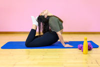 Flexible Woman practicing stretching exercises On Yoga Mat.
