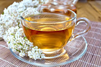 Tea with yarrow in cup on bamboo napkin