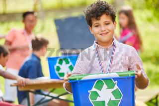 Junge trägt Kiste mit Recycling Symbol