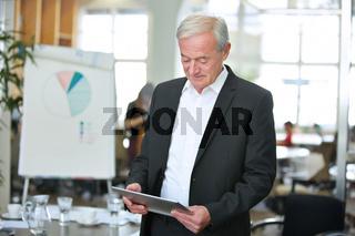 Geschäftsmann im Büro mit Tablet Computer